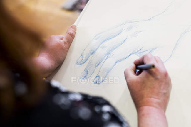 High angle close-up of artist drawing hand in art class. — Stock Photo