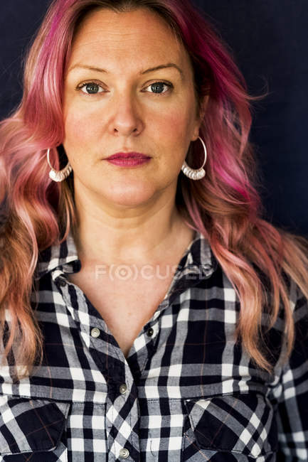 Portrait of woman with long wavy hair with pink streaks in black and white checkered shirt and hoop earrings. — Stock Photo