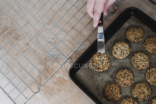 High angle view of person hand removing freshly baked seeded crackers from baking tray. — Stock Photo