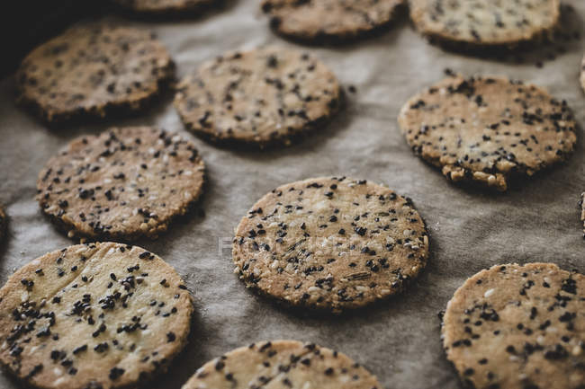 Close-up of freshly baked seeded crackers on baking tray. — Stock Photo