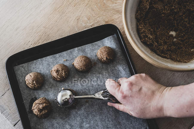 High angle close-up of person hand putting chocolate cookie dough on baking tray with scoop. — Stock Photo