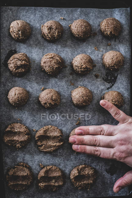 High angle close-up of person hand putting chocolate cookie dough on baking tray. — Stock Photo