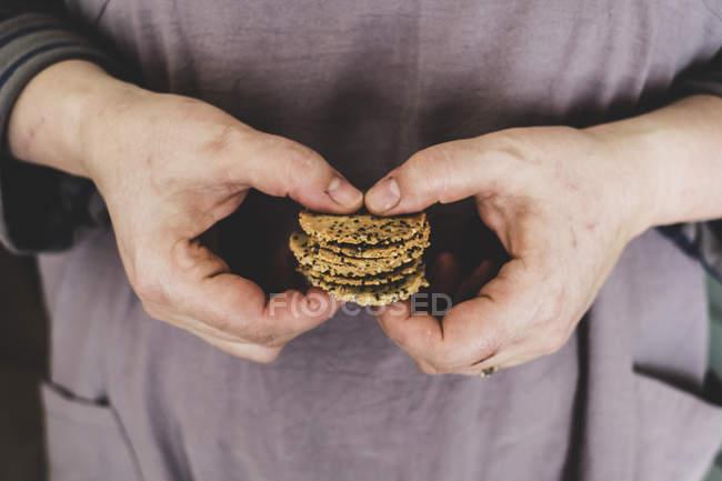 Gros plan de la personne tenant une petite pile de craquelins fraîchement cuits . — Photo de stock