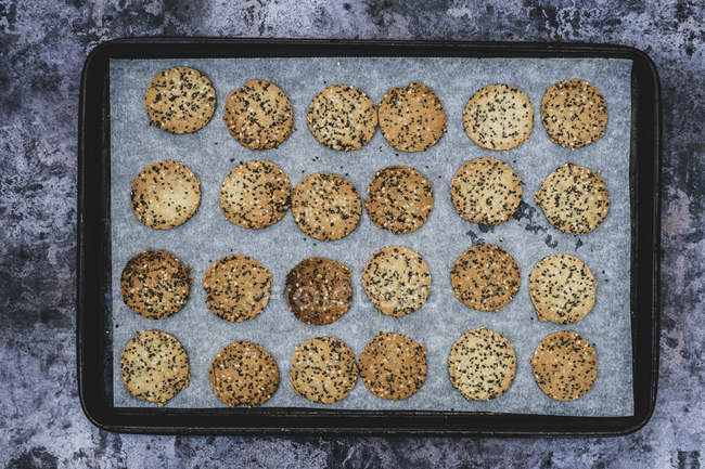 High angle view of freshly baked seeded crackers on baking tray. — Stock Photo