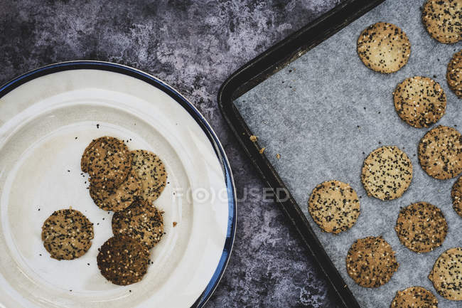 High angle view of freshly baked seeded crackers on plate and baking tray. — Stock Photo