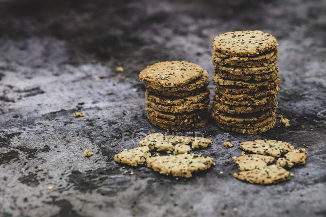 High angle close-up of stacks of freshly baked seeded crackers. — Stock Photo