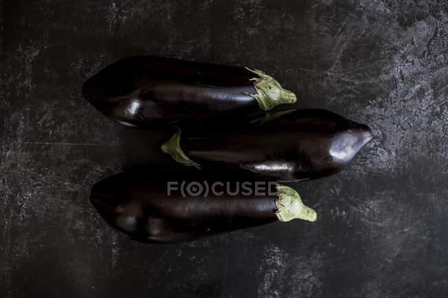 Three glossy purple aubergines on grey slate background — Stock Photo