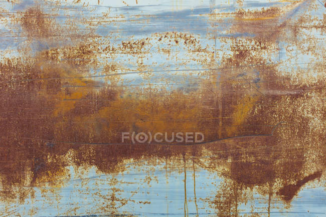 Pattern of brown rusting patches on old metal wall. — Stock Photo