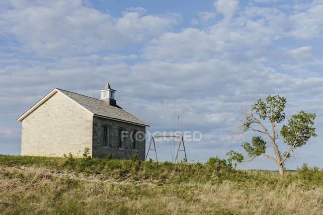 Hoch Gras Prärie bewahren historische Schulgebäude und Baumwollbaum im Frühjahr, große Ebenen, Kansas, USA. — Stockfoto
