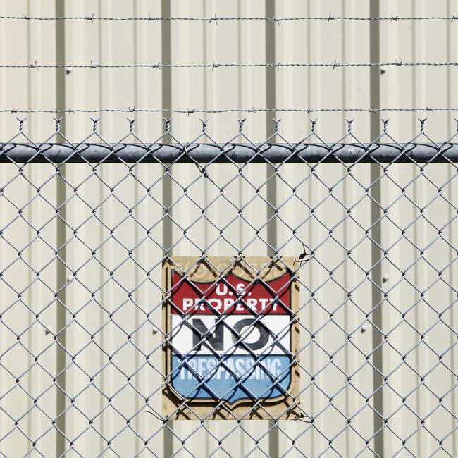 Предупреждающий знак и забор металлической цепи — стоковое фото