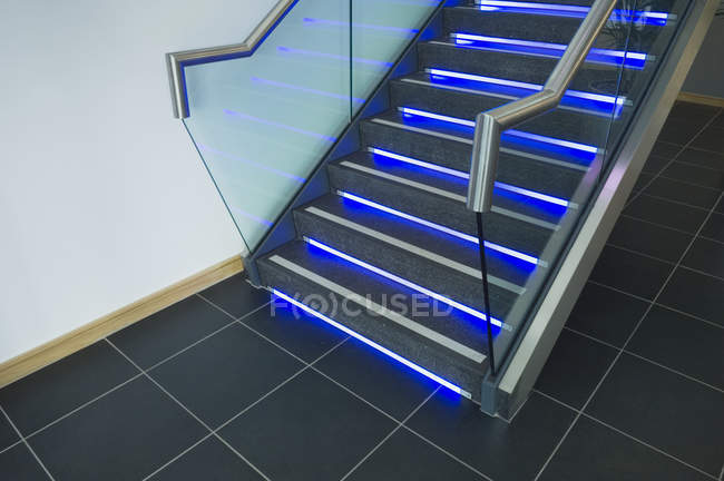 Modern office staircase with blue neon illumination — Stock Photo