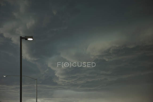 Dramatic storm clouds approaching street light posts in city — Stock Photo