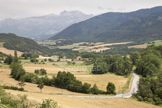 Vale com campos e fazendas e montanhas à distância, França — Fotografia de Stock