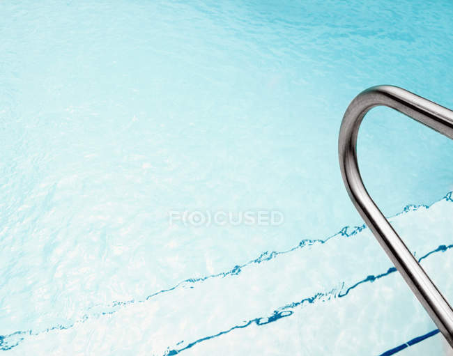 Swimming pool steps and railing with clear water — Stock Photo