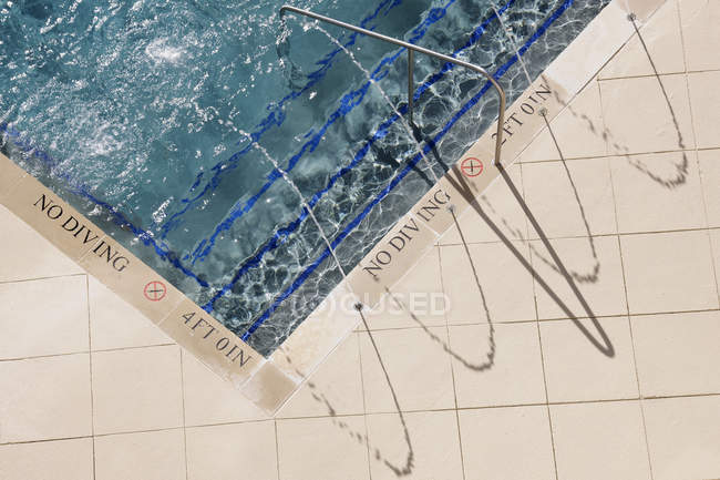 Swimming pool steps in water with railing and No Diving warning sign — Stock Photo