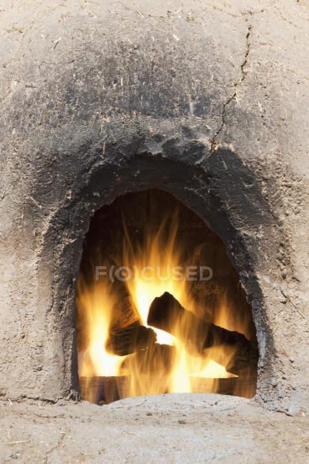Adobe піч з колоди і вогнем, Taos, Нью-Мексико, Сполучені Штати — стокове фото
