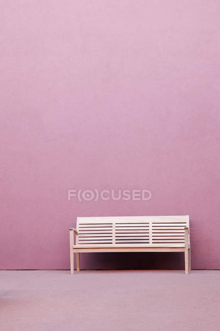 White bench in front of pink wall of building — Stock Photo