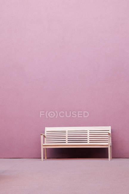 Banco blanco frente a la pared rosa del edificio - foto de stock
