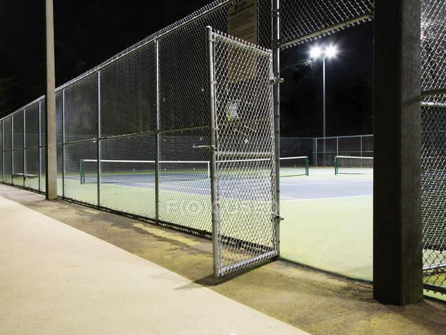 Porta aperta all'ingresso del campo da tennis di notte — Foto stock