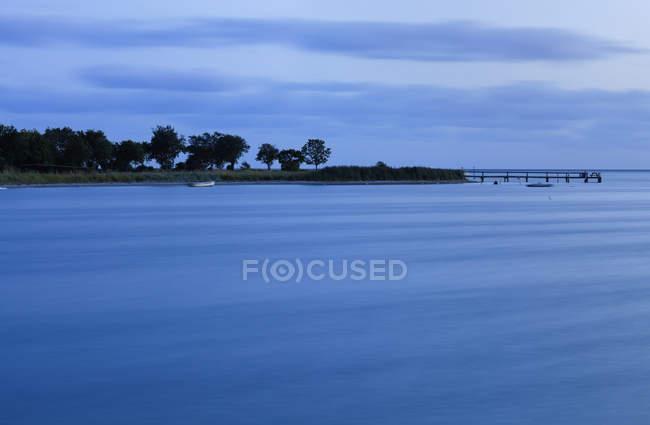 Crépuscule au-dessus de la surface et du littoral calmes d'eau avec des arbres et des bateaux amarrés au large au Danemark — Photo de stock