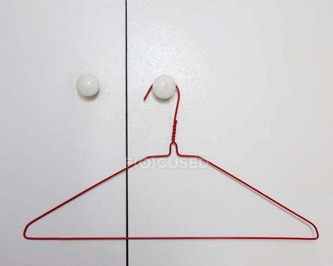 Red wire hanger hanging on doorknob of white door — Stock Photo