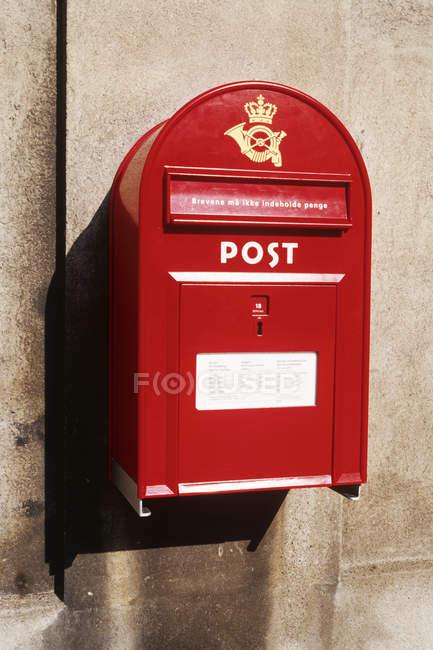 Postbox vermelho montado na parede cinzenta da cidade — Fotografia de Stock