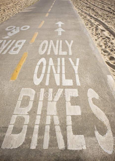 Велосипедная дорожка с надписями на песчаном пляже со следами — стоковое фото