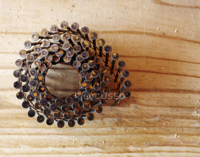 Coiled framing nails in wooden board surface, close-up — Stock Photo