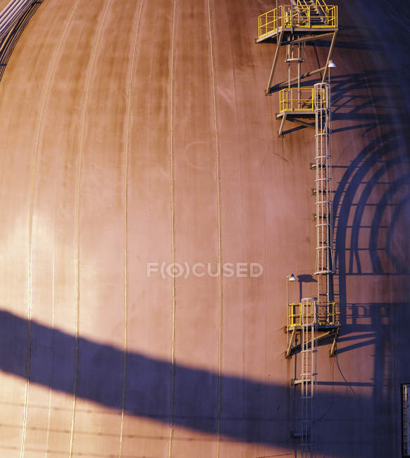 Ladder on side of industrial building with shadow in sunlight — Stock Photo