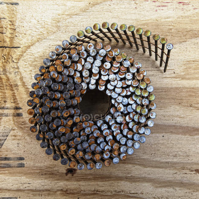 Clavos de encuadre en espiral en superficie de madera, primer plano - foto de stock