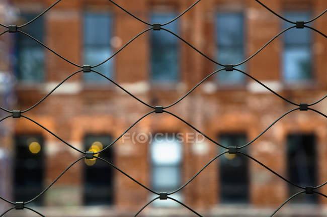 Городская сетка ограждения со зданием в селективном фокусе, Нью-Йорк, Нью-Йорк, США — стоковое фото