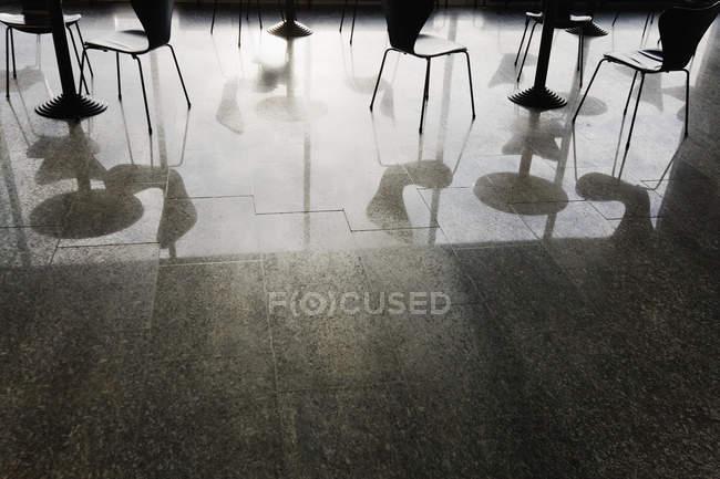 Riflessione di tavoli e sedie sul pavimento lucido del ristorante — Foto stock