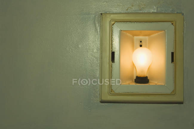 Incandescent light bulb in wall, close-up — Stock Photo