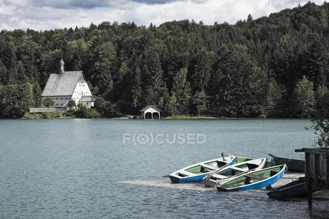 Маленькие лодки и часовня на берегу озера, озеро Вальченси, Бавария, Германия, Европа — стоковое фото
