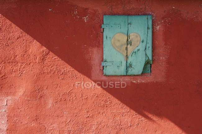 Red wall with shuttered window with painted heart — Stock Photo
