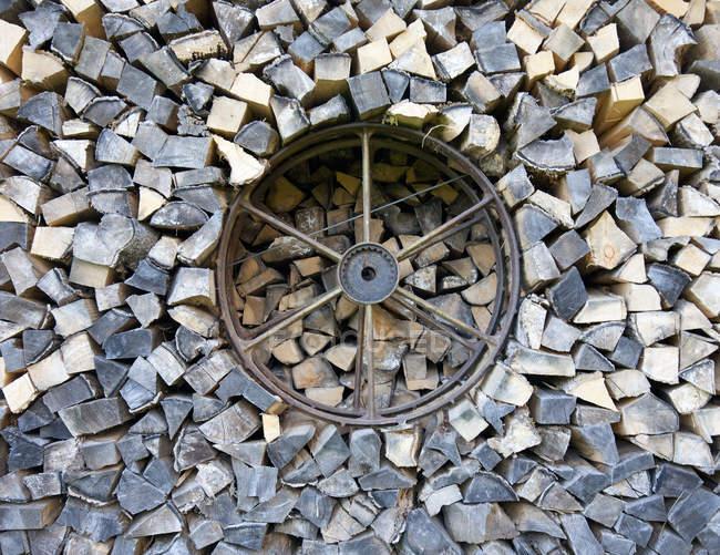 Bois de chauffage haché empilé et roue de cru — Photo de stock