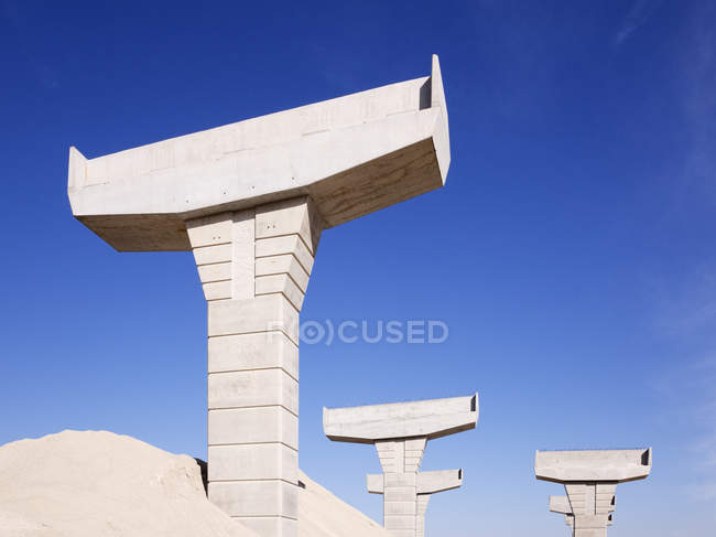 Highway overpass supports buried in sand against blue sky, McKinney, Texas, United States — стокове фото