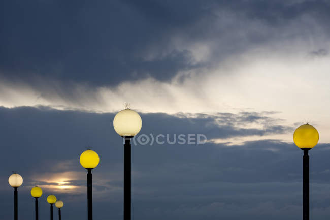 Round street lights illuminating at dusk against cloudy sky — Stock Photo