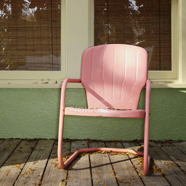 Pink metal chair on building porch — Stock Photo