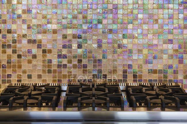 Газова плита і барвиста кахельна стіна в приміщенні — стокове фото
