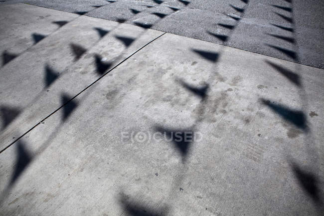 Flags casting shadows on concrete flooring on parking lot — Stock Photo