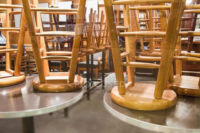 Chaises assises empilées sur des tables rondes à l'intérieur — Photo de stock