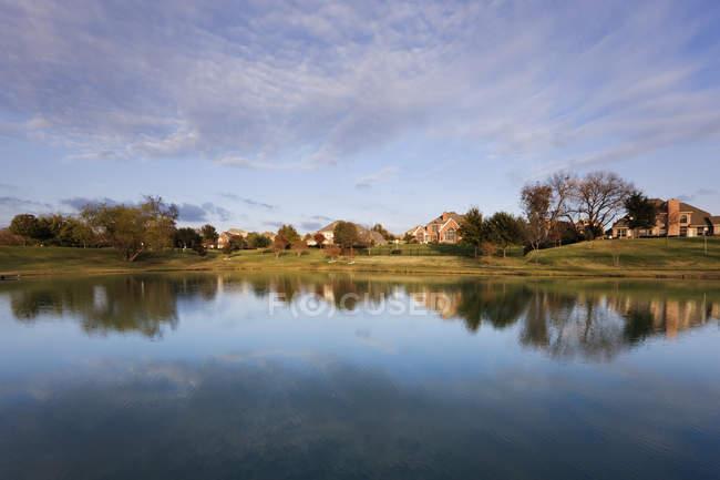 Case che si riflettono in acqua di stagno nel villaggio — Foto stock