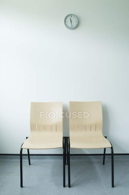 Two chairs and clock against white wall — Stock Photo