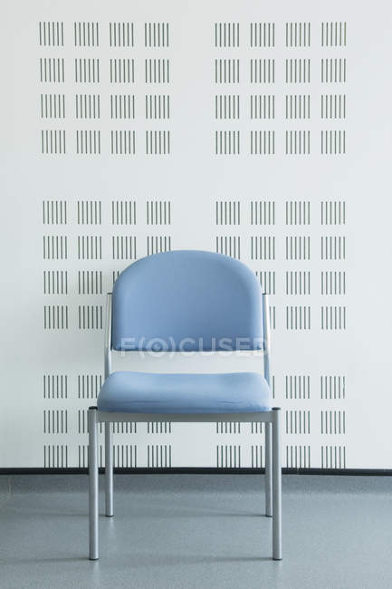Синій простий стілець проти сучасної стіни — стокове фото