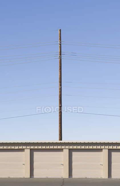 Power lines and pole over bay doors against blue sky — Stock Photo