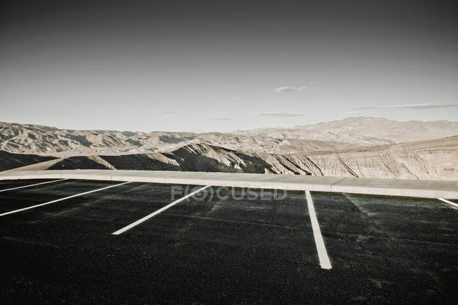 Desert parking spaces with hills and arid mountains in distance, Death Valley, California, United States — Stock Photo