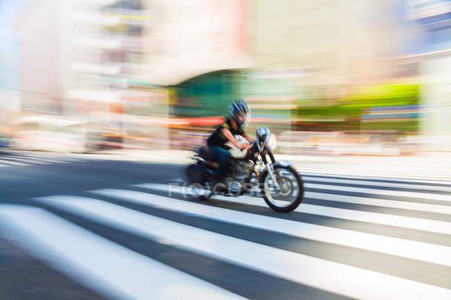Bewegung verschwommene Aufnahme von Motorrad und Mann mit Geschwindigkeit auf Fußgängerüberweg in Tokio, Japan. — Stockfoto