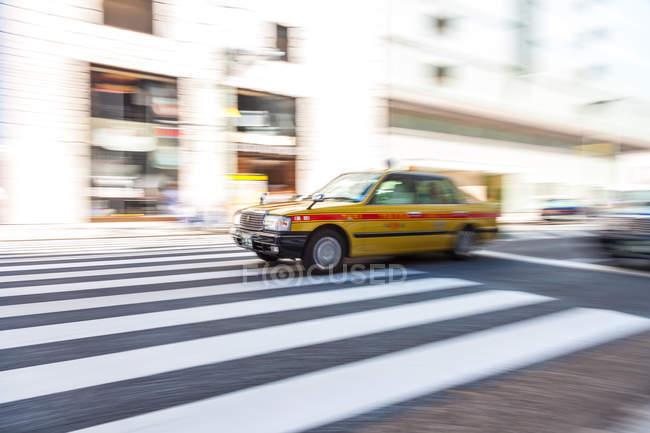 Bewegung verschwommene Aufnahme eines gelben Taxis auf einem Fußgängerüberweg, Tokio, Japan. — Stockfoto
