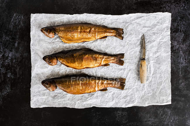 High angle close-up of three fresh smoked whole trouts and knife on white paper. — Stock Photo